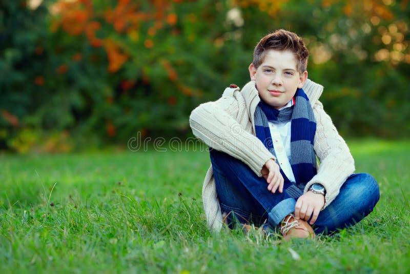 Stilfull tonårs- pojke på grönt gräs arkivbilder