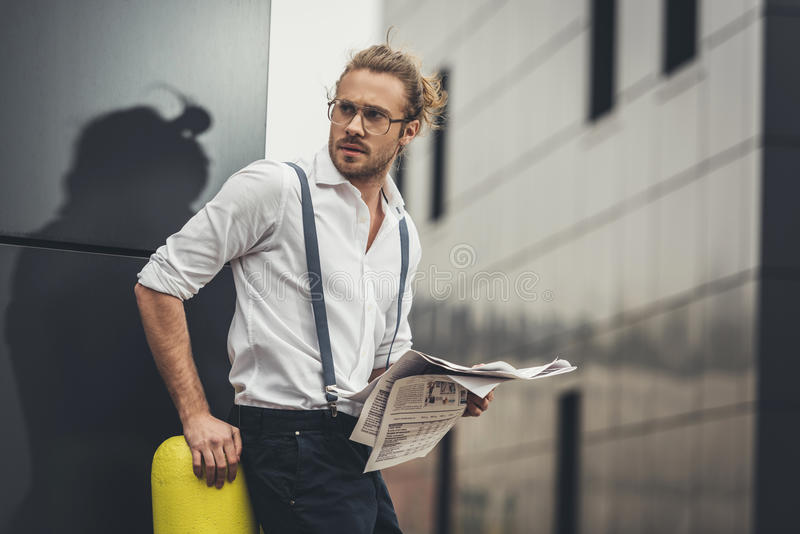 Stilfull ung affärsman i glasögon som läser tidningen och bort ser arkivfoton
