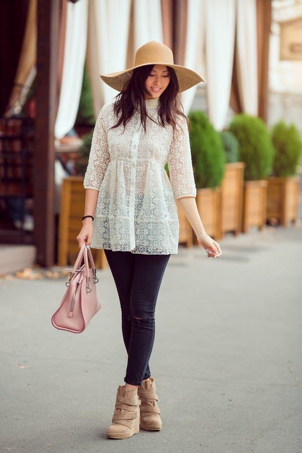 Stilfull ung asiatisk flicka som går på stadsgatan mot kaféfasad arkivbild