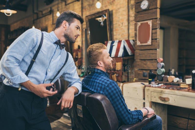 Stilfull ung barberare med sax som står bak kunden som sammanträde royaltyfri foto