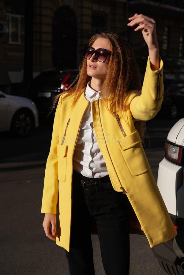 Stilfull ung caucasian flicka på gatan som fångar taxien på solig dag arkivbild