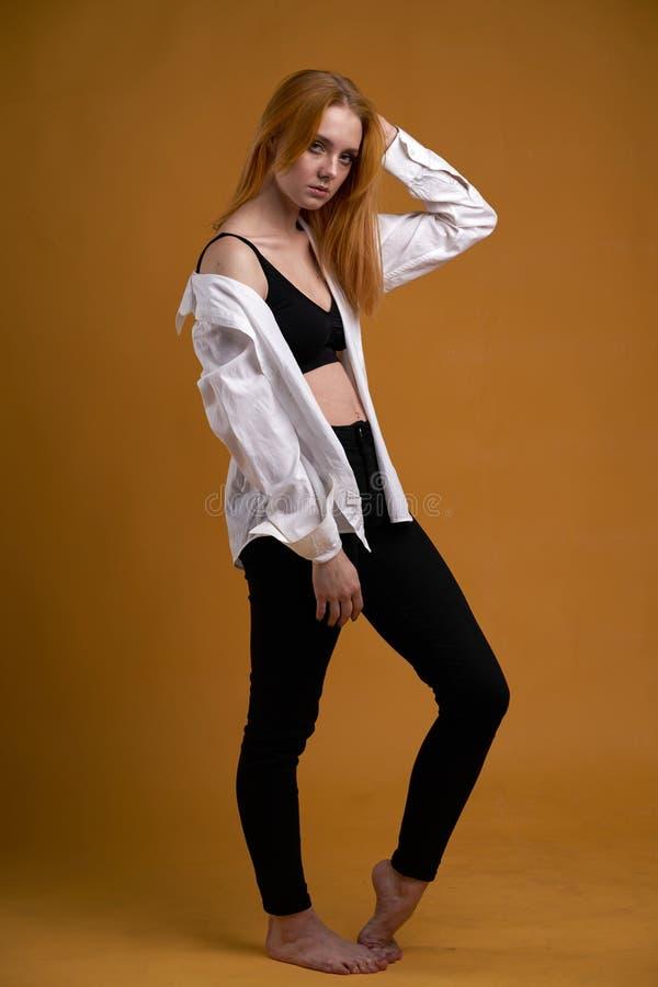Stilfull ung flicka med lockigt h?r och att le cutely som poserar, p? gul bakgrund arkivbilder