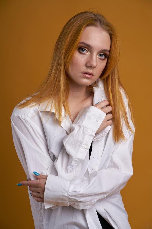 Stilfull ung flicka med lockigt h?r och att le cutely som poserar, p? gul bakgrund royaltyfri foto