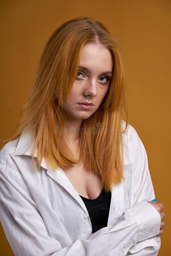 Stilfull ung flicka med lockigt h?r och att le cutely som poserar, p? gul bakgrund arkivbild