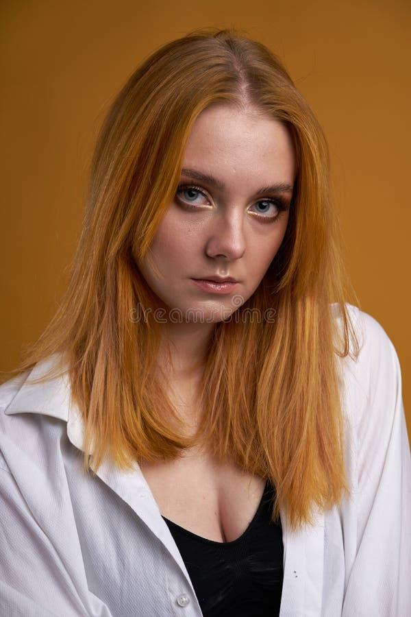 Stilfull ung flicka med lockigt h?r och att le cutely som poserar, p? gul bakgrund royaltyfria foton