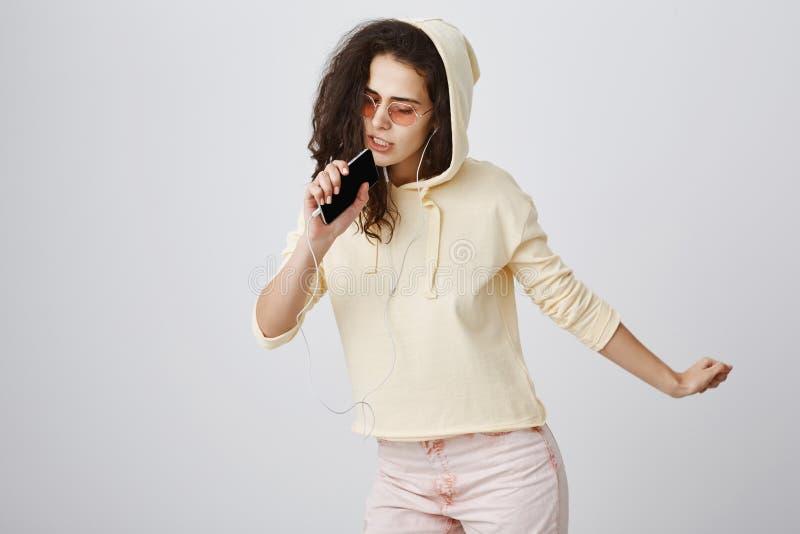 Stilfull ung kvinna som sjunger längs hennes favorit- spår Stående av den mjuka trendiga flickan i moderiktig solglasögon och arkivbilder