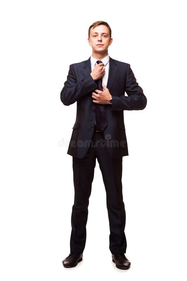 Stilfull ung man i dräkt och band kvinna för white för affärspennstil Den stiliga mannen står, ser kameran och fixar hans band royaltyfria foton