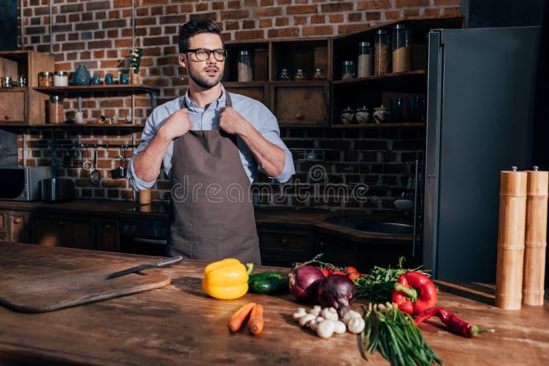stilfull ung man i förkläde på kök med nya grönsaker royaltyfri fotografi