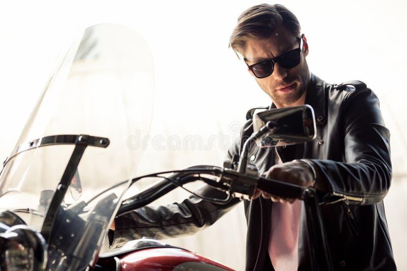 Stilfull ung man, i solglasögon- och för läderomslag sammanträde på motorcykeln och att se kameran royaltyfria bilder
