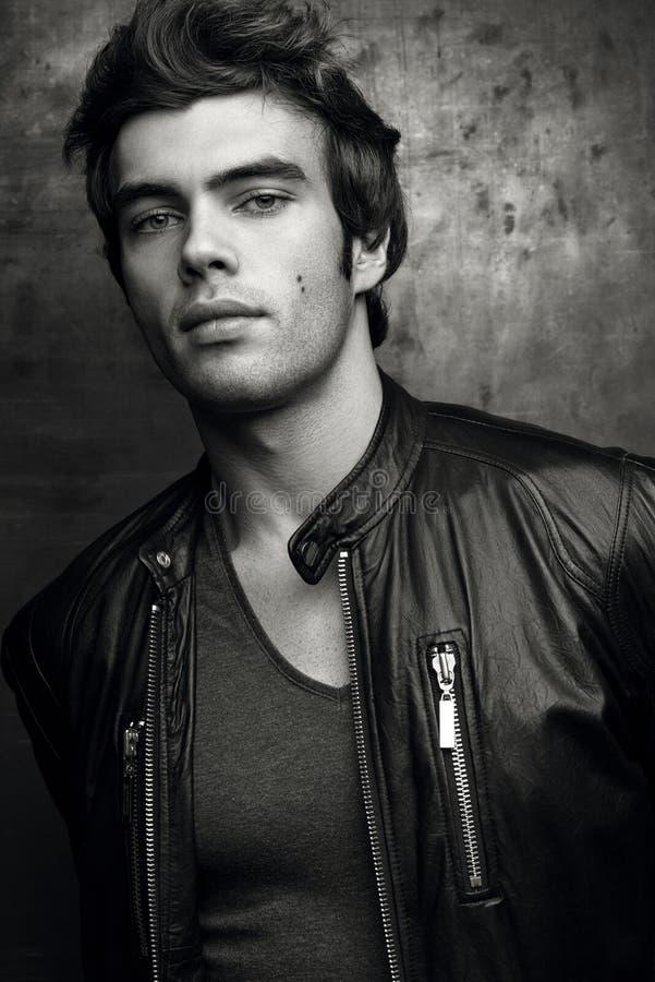 Stilfull ung man i svart läderomslag Svartvit kontrast royaltyfri bild