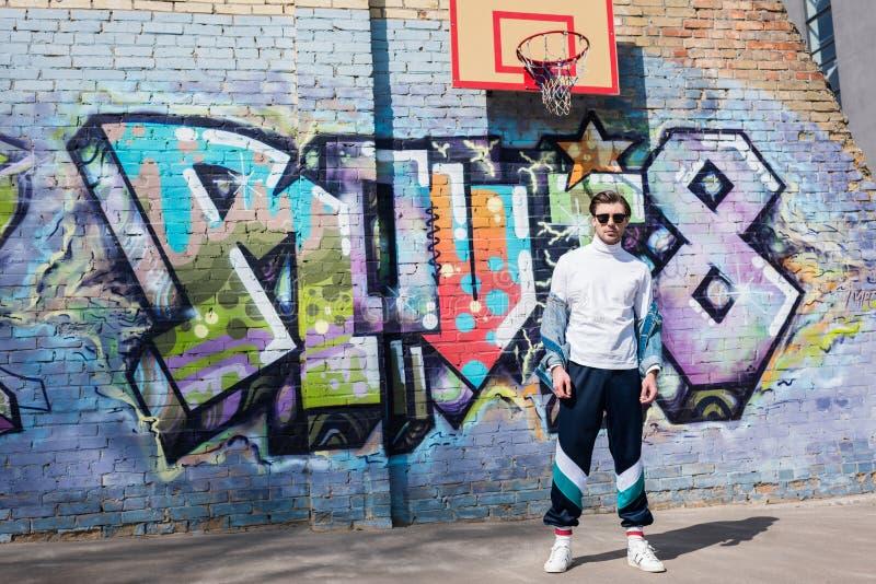 stilfull ung man i tappning som framme beklär av tegelstenväggen med grafitti fotografering för bildbyråer