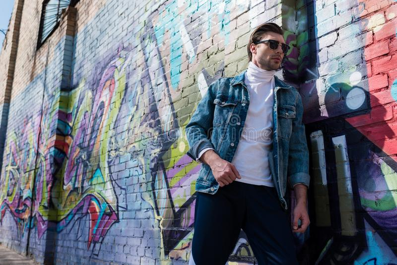 stilfull ung man i tappningkläder som lutar på tegelstenväggen royaltyfri bild