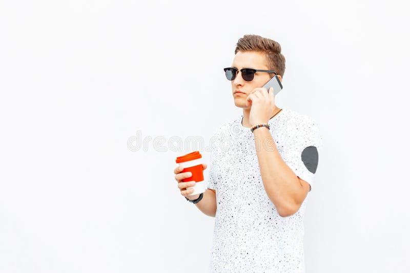 Stilfull ung man som rymmer en kopp kaffe i hand arkivfoto