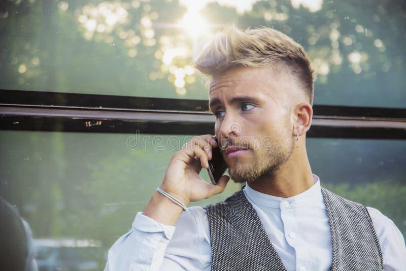 Stilfull ung man som talar på telefonen som är utomhus- mot exponeringsglas fotografering för bildbyråer