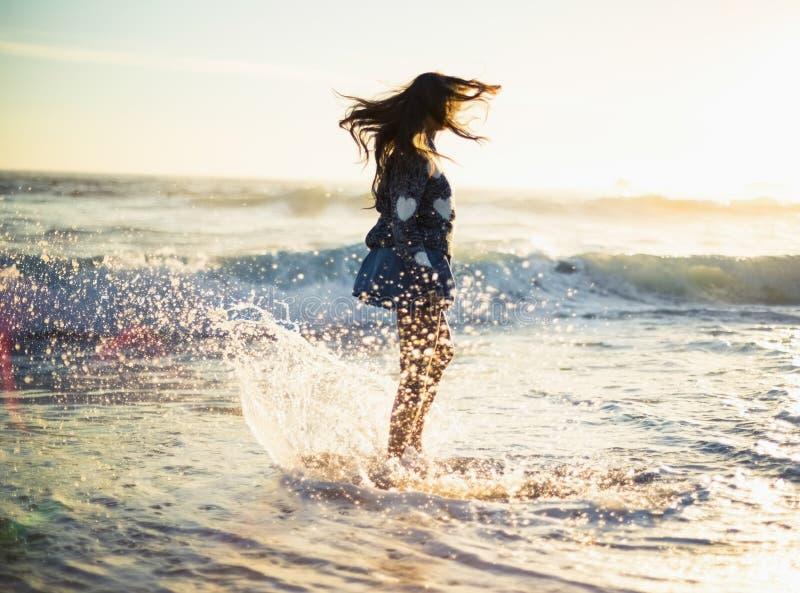 Stilfull ursnygg kvinna som tycker om i havet royaltyfri foto