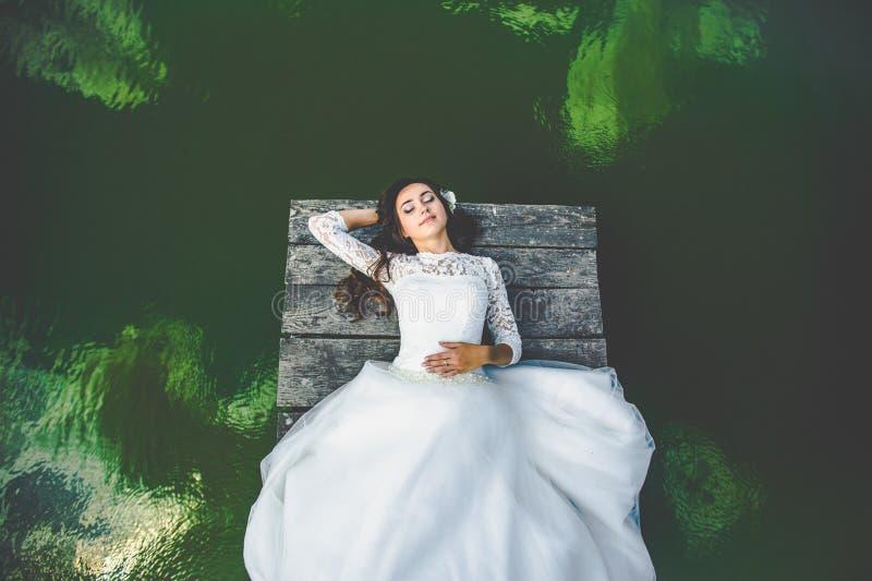 Stilfull ursnygg lycklig brunettbrud på pir på backgroen royaltyfria bilder