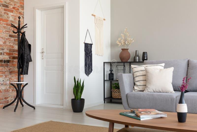 Stilfull vardagsrum med den gråa soffan och trätabellen, verkligt foto royaltyfri foto