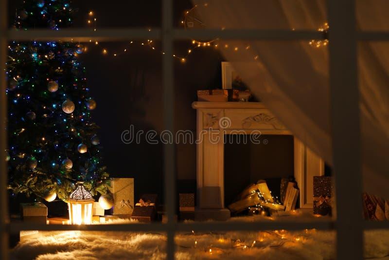 Stilfull vardagsruminre med den dekorerade julgranen och spisen på natten royaltyfria foton