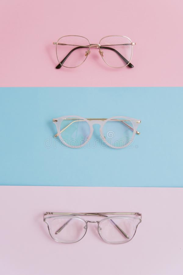Stilfulla bildexponeringsglas på en pastellfärgad bakgrund Tre par av exponeringsglas med linser på rosa och blåa bakgrunder stil arkivfoto