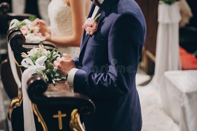 Stilfulla brölloppar som står i kyrkan för heligt äktenskap Härlig brud och brudgum som ber på träaltaret i kyrkan, bröllop arkivbild