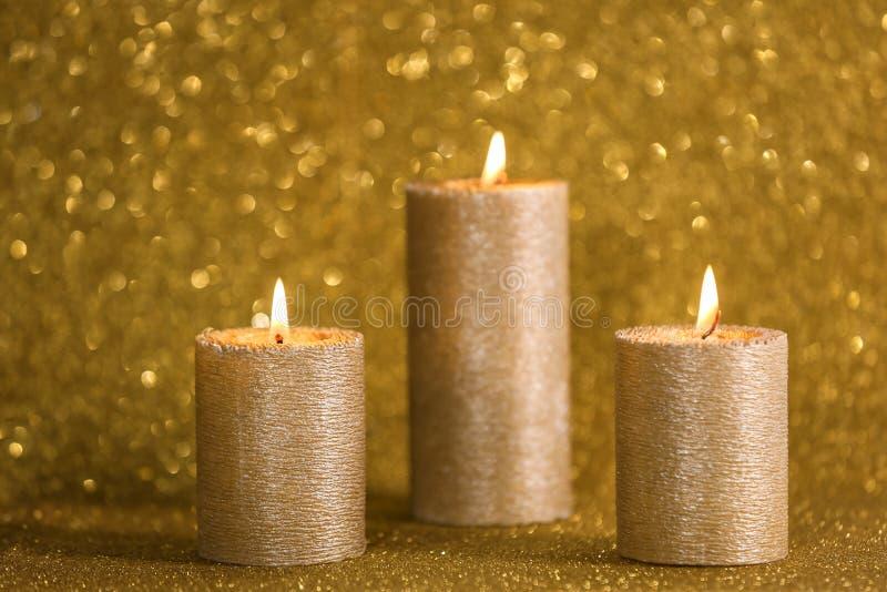 Stilfulla brinnande stearinljus på guld- skina royaltyfri foto