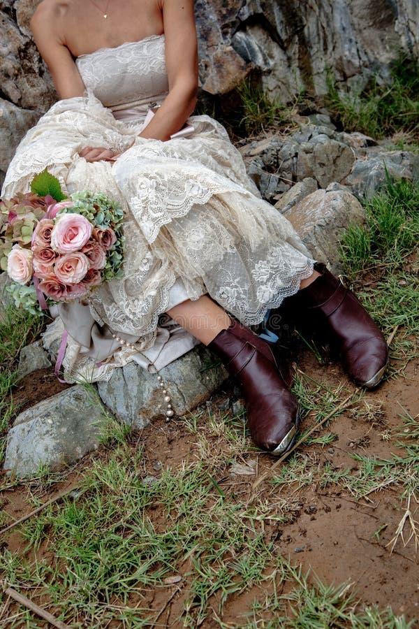 Stilfulla bruna kängor för västra brudar som rymmer en elegant blommabukett Sitta på ett moment i en tappningbröllopsklänning arkivbilder