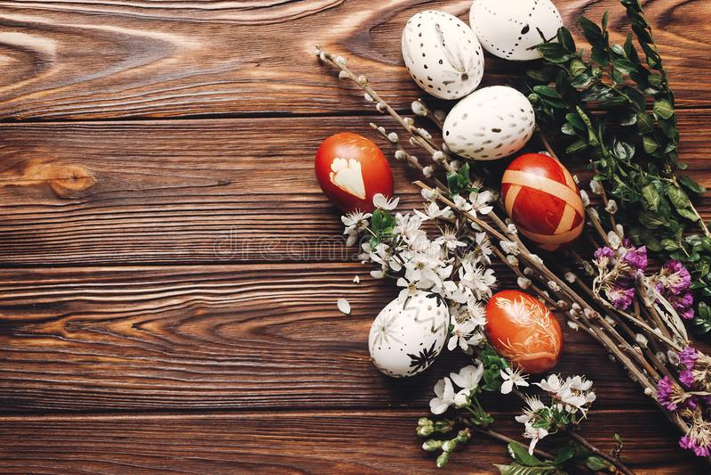Stilfulla easter ägg med vita blommor och knoppar på träbackgr arkivbilder