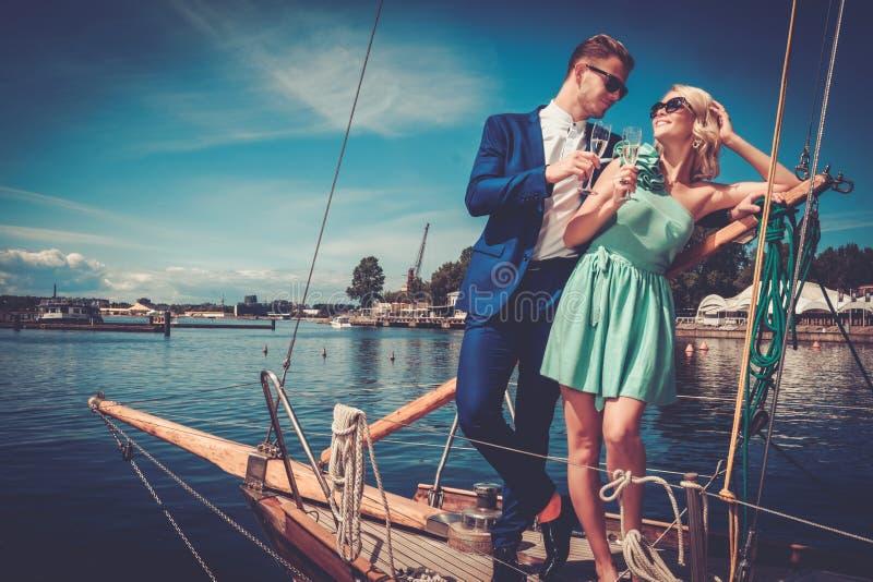 Stilfulla förmögna par på en lyxig yacht arkivfoto