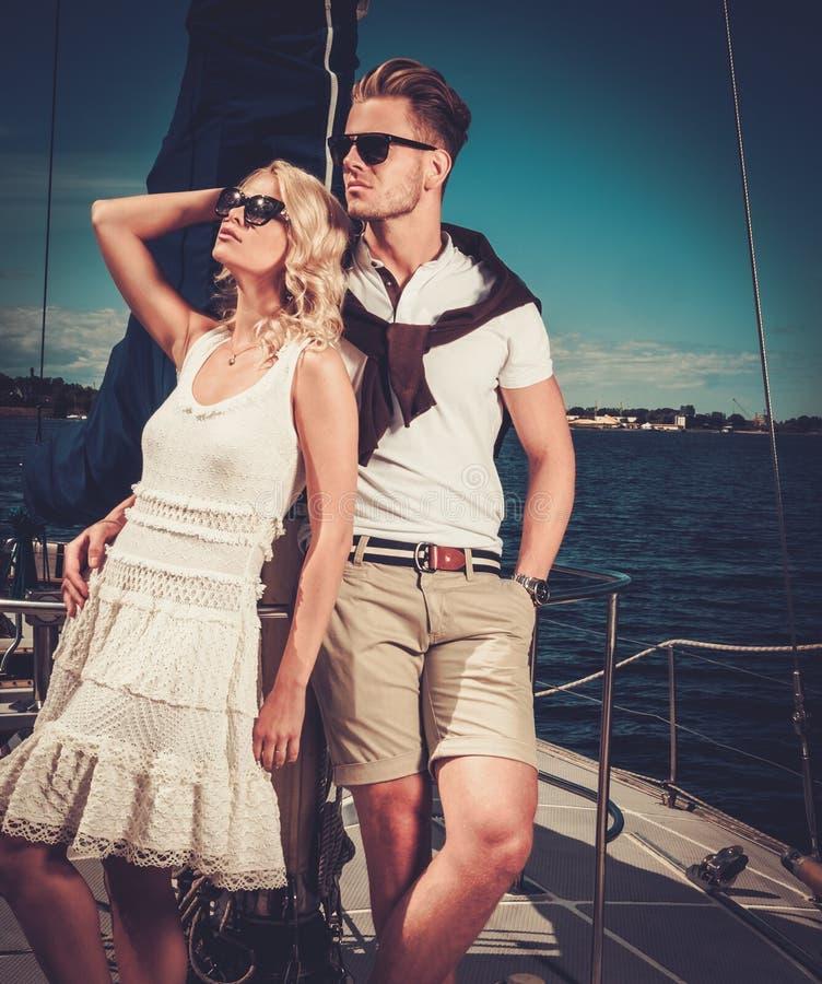Stilfulla förmögna par på yachten royaltyfria bilder