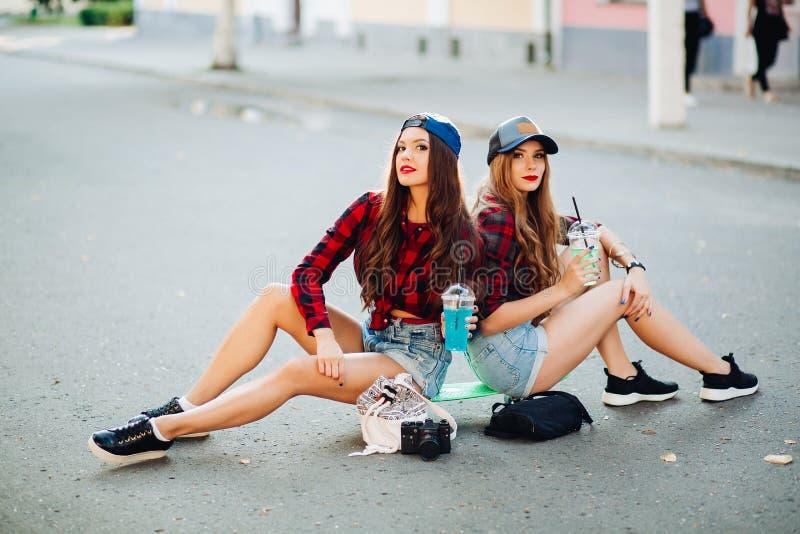 Stilfulla flickvänner som sitter på skateboarden på gatan royaltyfria foton