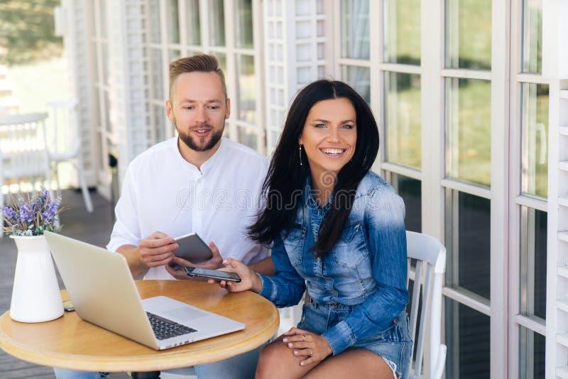 Stilfulla grabbar sitter på en tabell i ett kafé i den öppna luften som är lycklig att se en flickvän som har precis sammanfogat  royaltyfria bilder