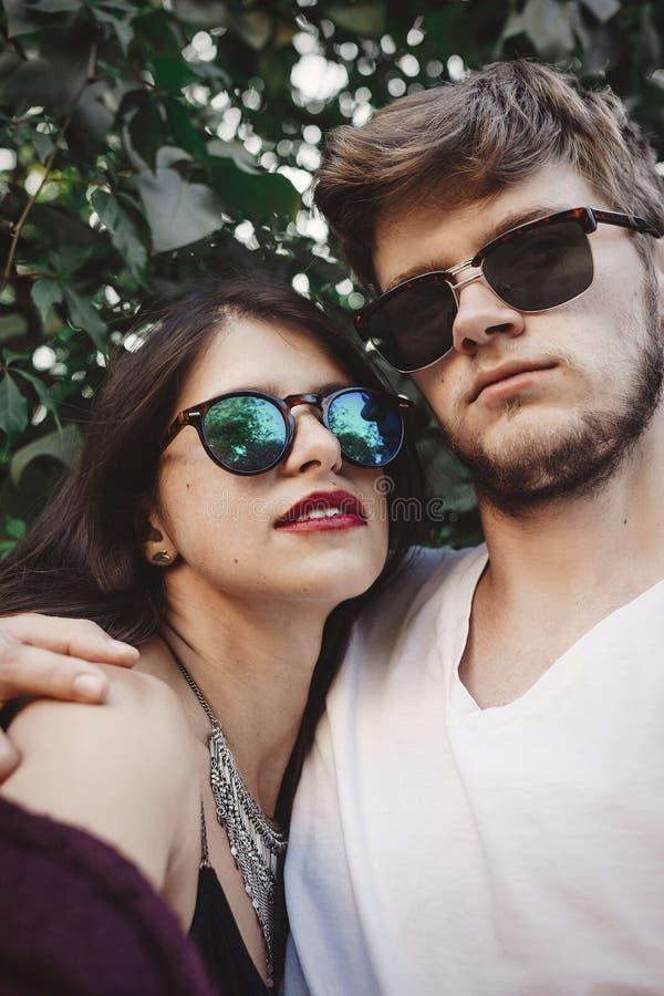 Stilfulla hipsterpar i solglasögon som ler och gör kall selfie Stående och posera för lyckliga familjpar förälskad görande själv fotografering för bildbyråer