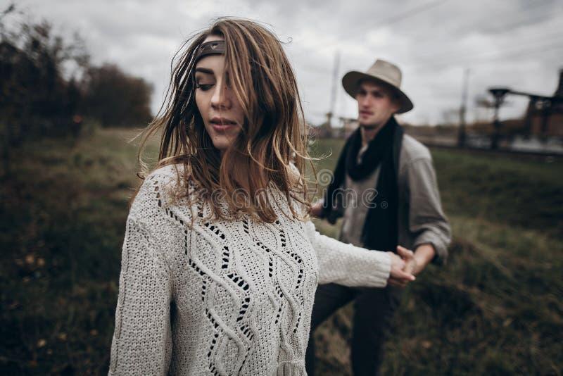 Stilfulla hipsterpar som sensually rymmer händer bohozigenarekvinna royaltyfri fotografi