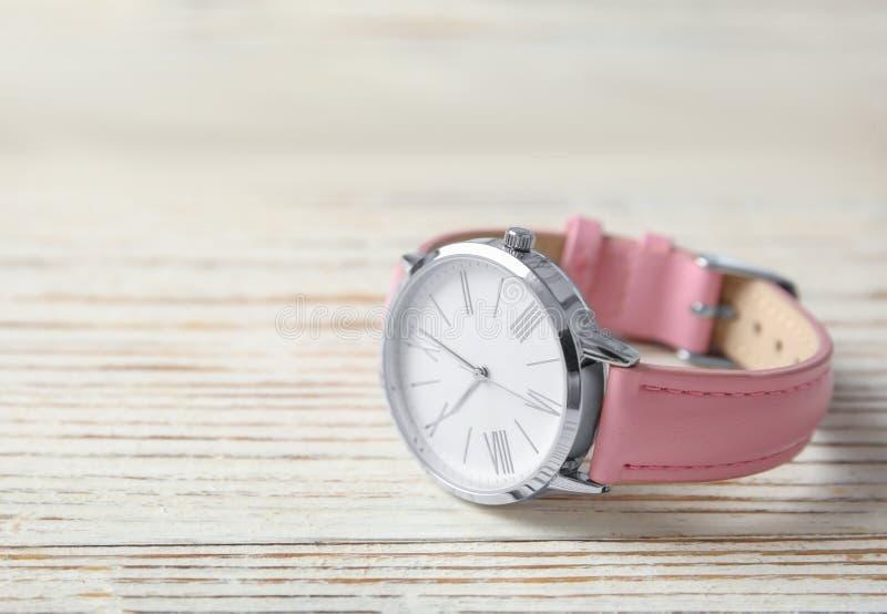Stilfulla kvinnors armbandsur på trätabellen, utrymme för text Mode royaltyfria bilder