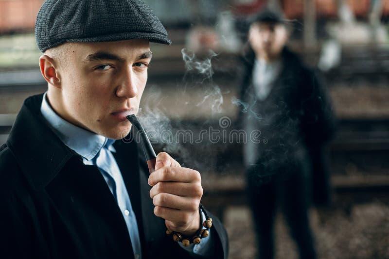 Stilfulla män som röker i retro kläder som poserar på bakgrund av raien royaltyfri bild