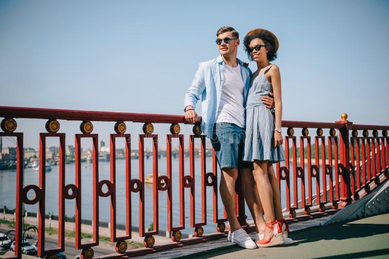 stilfulla multietniska par i solglasögonanseende royaltyfri bild