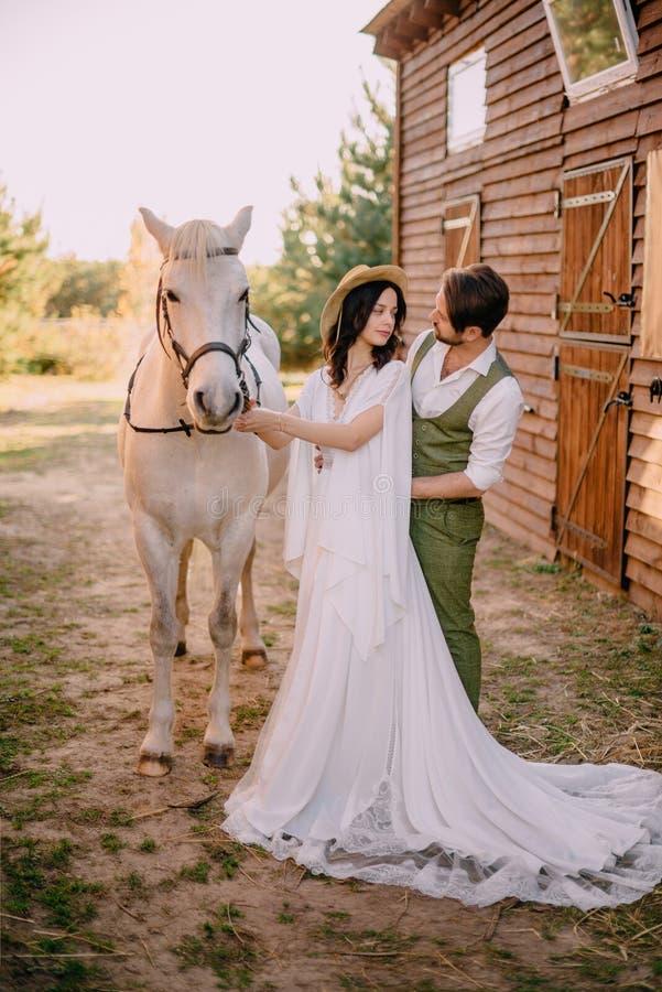 Stilfulla nygifta personer som kramar nära hästen, landsstil royaltyfria foton
