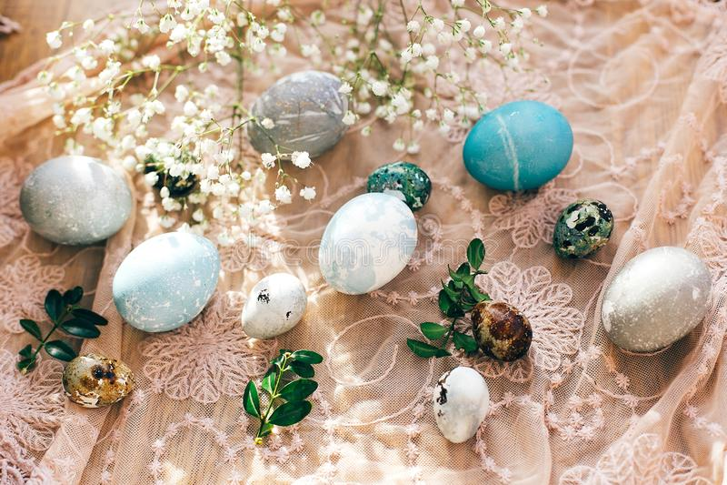 Stilfulla påskägg med vårblommor och gröna buxusfilialer på lantligt tyg i soligt ljus på trä moderna färgrika ägg royaltyfri bild