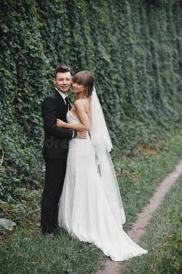 Stilfulla par av nygifta personer p? deras gifta sig dag Lycklig ung brud, elegant brudgum och br?llopbukett royaltyfria bilder