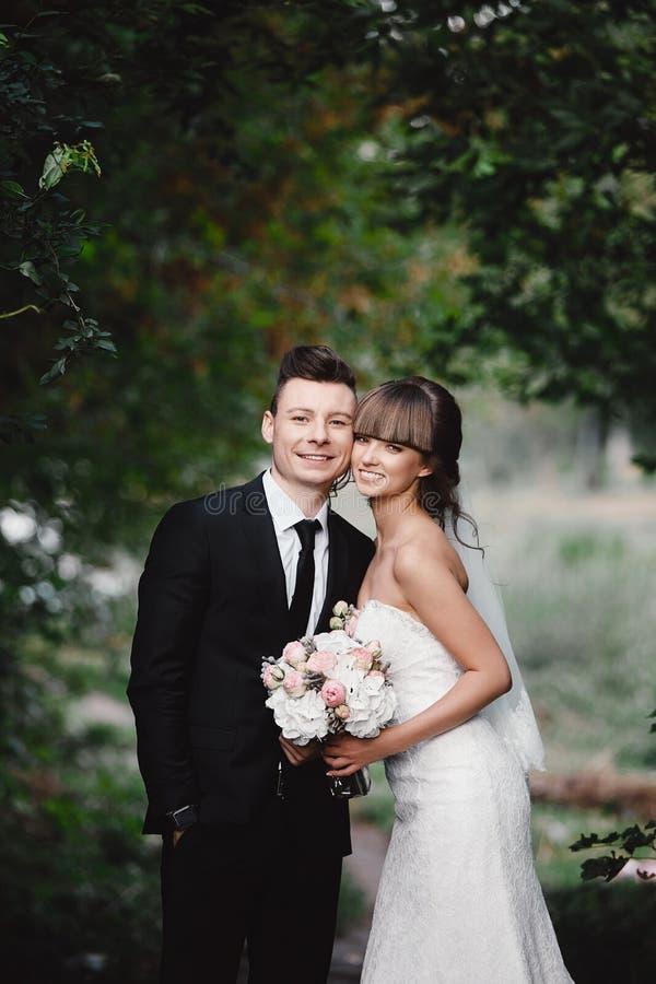Stilfulla par av nygifta personer p? deras gifta sig dag Lycklig ung brud, elegant brudgum och br?llopbukett royaltyfri fotografi