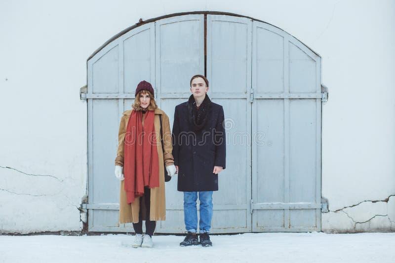 Stilfulla par i det klassiska följet som står near vit historisk byggnad Trendiga vinterkläder fotografering för bildbyråer