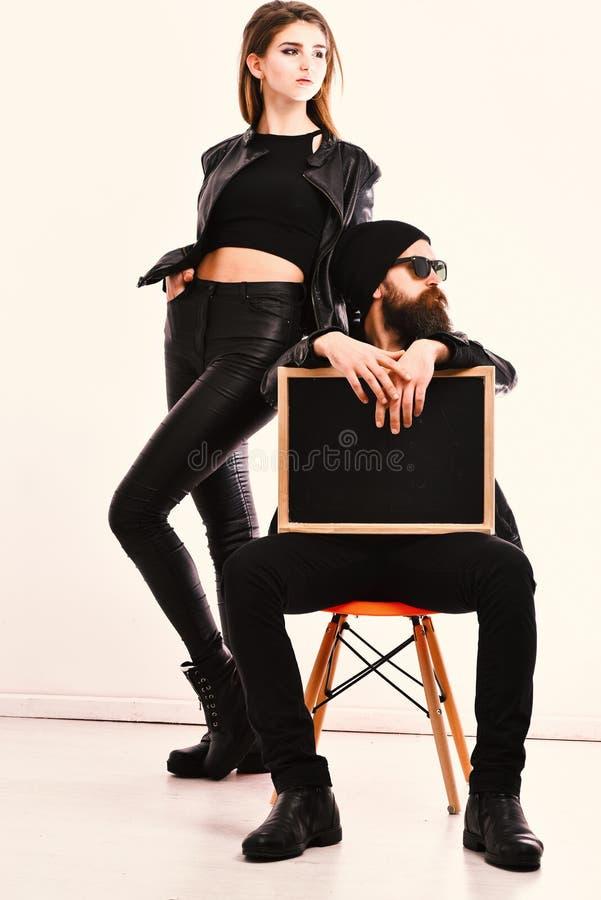 Stilfulla par som bär svarta läderomslag på vit bakgrund fotografering för bildbyråer