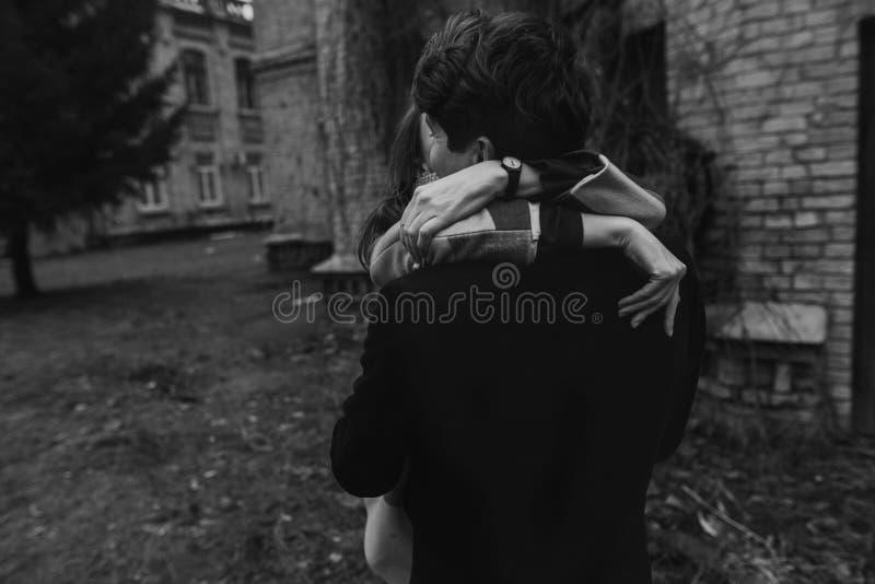 Stilfulla par som har roligt och kramar i höst, parkerar räcker clos royaltyfri bild