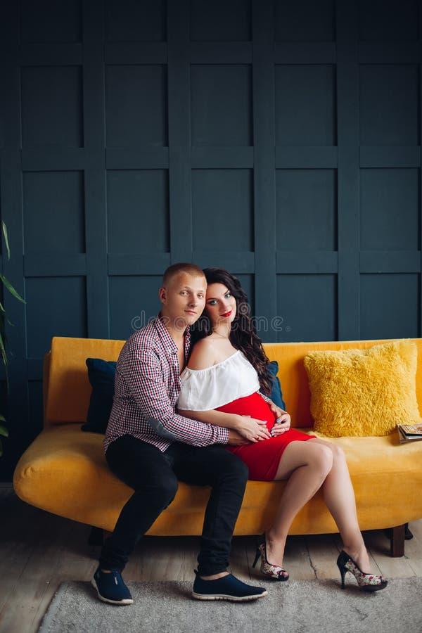 Stilfulla par som sitter på den gula soffan och ser kameran royaltyfria bilder