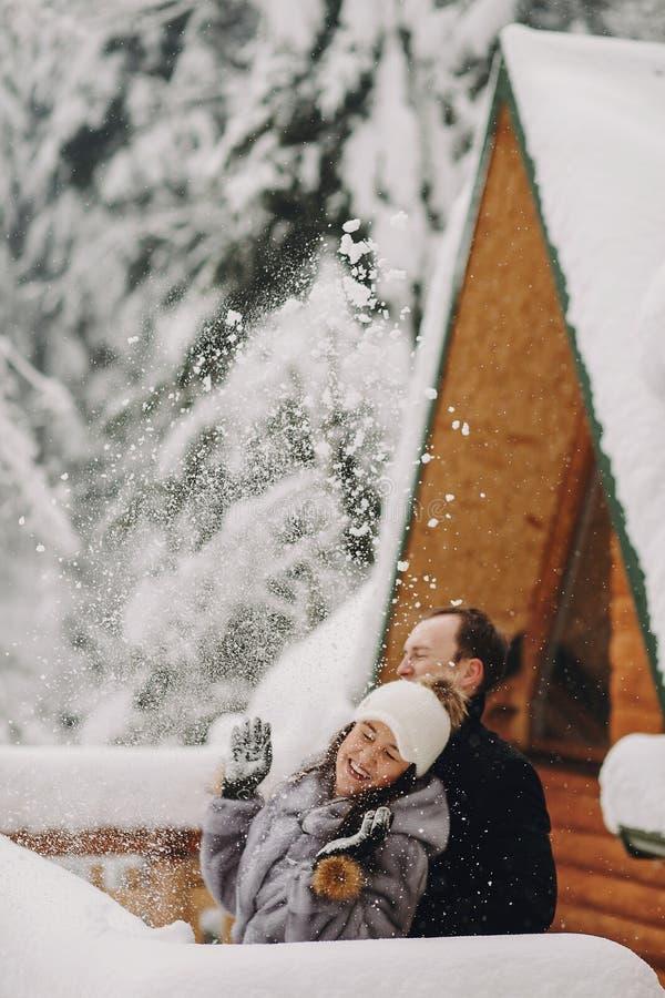 Stilfulla par som spelar med den insnöade träkabinen på bakgrundsnolla royaltyfria bilder