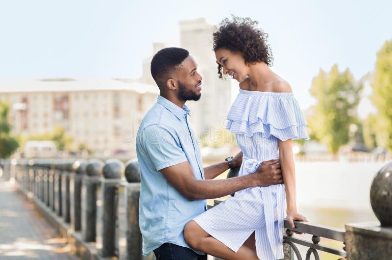 Stilfulla unga par som kramar, medan gå i stad royaltyfri fotografi