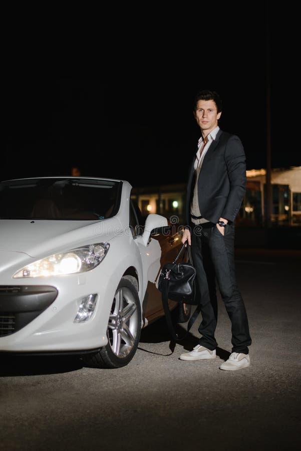 Stilfullt anseende för ung man bredvid hans vita cabriolet uteliv Affärsman i dräkt i lyxig bil arkivfoto