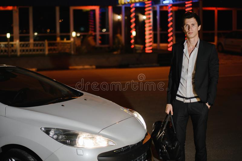 Stilfullt anseende för ung man bredvid hans vita cabriolet uteliv Affärsman i dräkt i lyxig bil royaltyfria bilder