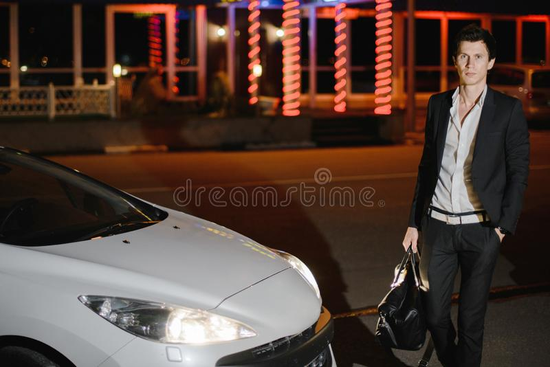 Stilfullt anseende för ung man bredvid hans vita cabriolet uteliv Affärsman i dräkt i lyxig bil fotografering för bildbyråer