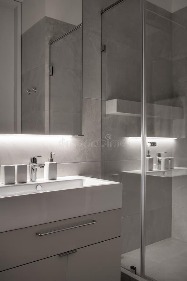 Stilfullt badrum i modern stil med belade med tegel väggar och belysning arkivbilder